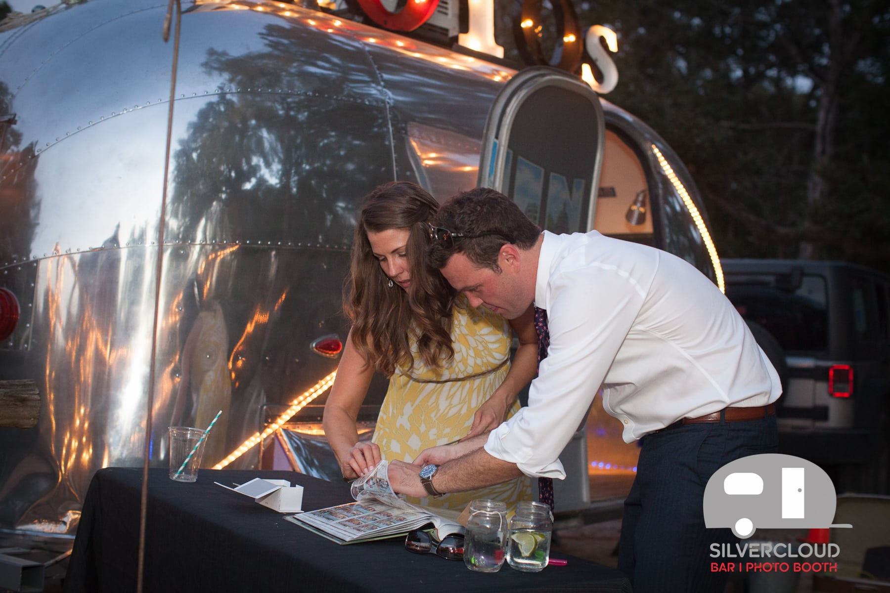 Guests write notes to the bride and groom outside the Silvercloud photo booth trailer